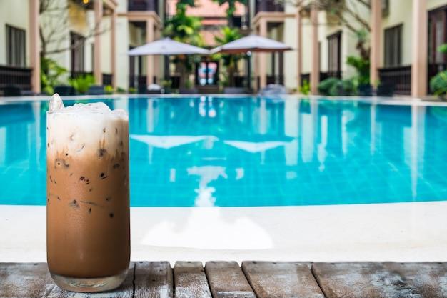 Een glas ijskoffie op de houten lijst door de pool