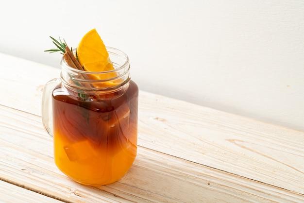 Een glas ijskoude americano zwarte koffie en een laagje sinaasappel- en citroensap versierd met rozemarijn en kaneel op houtachtergrond