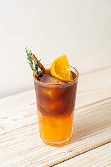 Een glas ijskoude americano zwarte koffie en een laagje sinaasappel- en citroensap versierd met rozemarijn en kaneel op houten achtergrond