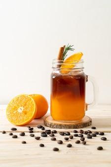 Een glas ijskoude americano zwarte koffie en een laagje sinaasappel- en citroensap versierd met rozemarijn en kaneel op houten oppervlak
