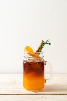 Een glas ijskoude americano zwarte koffie en een laagje sinaasappel- en citroensap versierd met rozemarijn en kaneel op houten tafel