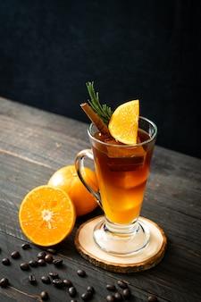 Een glas ijskoude americano zwarte koffie en een laagje sinaasappel- en citroensap versierd met rozemarijn en kaneel