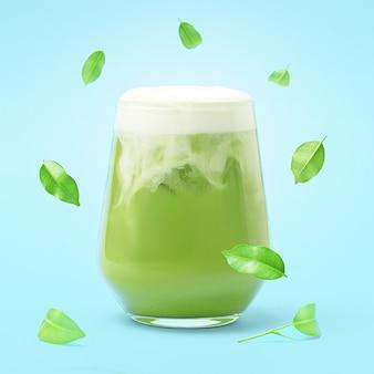 Een glas ijskoude matcha latte op een blauwe achtergrond met vallende bladeren.