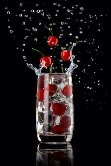 Een glas kersenlimonade, spetterend in verschillende richtingen en drie kersenbessen die in het glas vallen