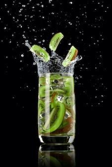 Een glas kiwi-limonade met ijs, spetterend in verschillende richtingen en drie plakjes kiwi die in het glas vallen