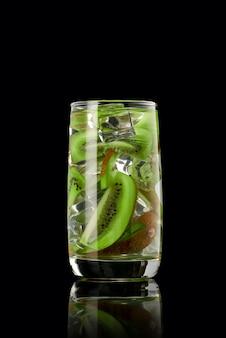 Een glas kiwilimonade met ijs op een zwarte