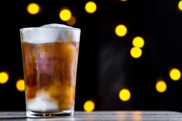Een glas koffie, koude cocktail met schuim en ijs