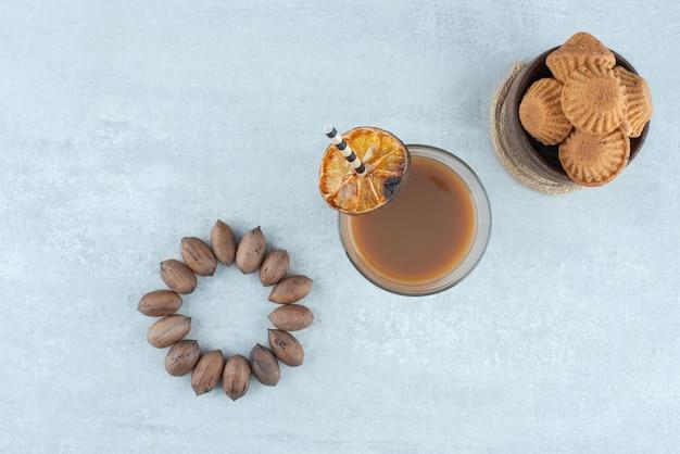 Een glas koffie met noten en koekjes