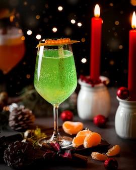 Een glas koolzuurhoudende groene drank en mandarijn