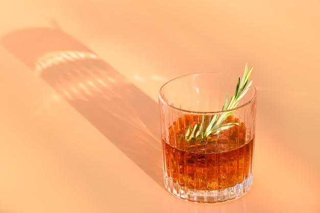 Een glas koude whisky versiert rozemarijn op beige achtergrond met zonnige schaduw.