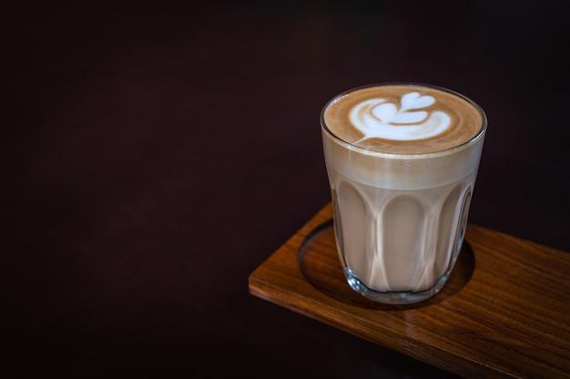 Een glas latte-kunst op houten plaat met donkere achtergrond