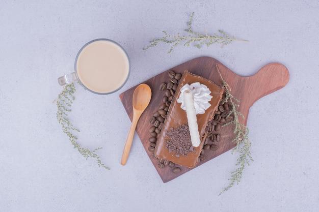 Een glas latte met een plakje karameltaart