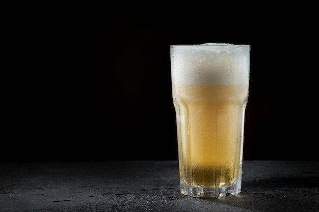 Een glas licht bier op donker