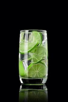Een glas limoenlimonade met ijs op een zwarte
