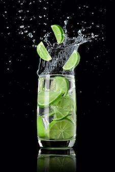 Een glas limoenlimonade met ijs, spetterend in verschillende richtingen en drie schijfjes limoen die in het glas vallen