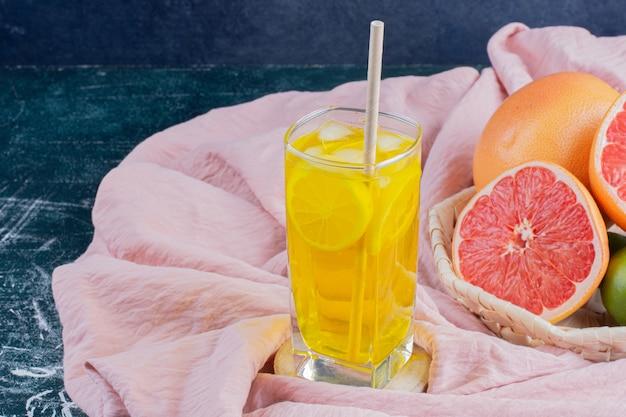 Een glas limonade met schijfjes citroen en grapefruits op marmeren oppervlak.