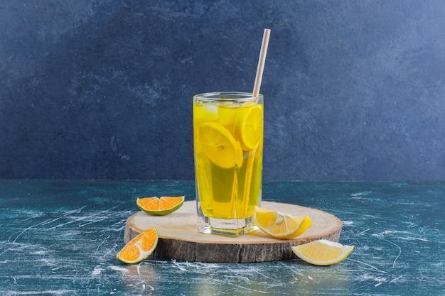 Een glas limonade met schijfjes citroen op marmeren oppervlak.