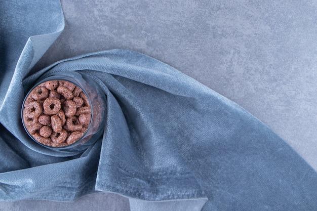 Een glas maïs ringen op een stuk stof, op de blauwe achtergrond.