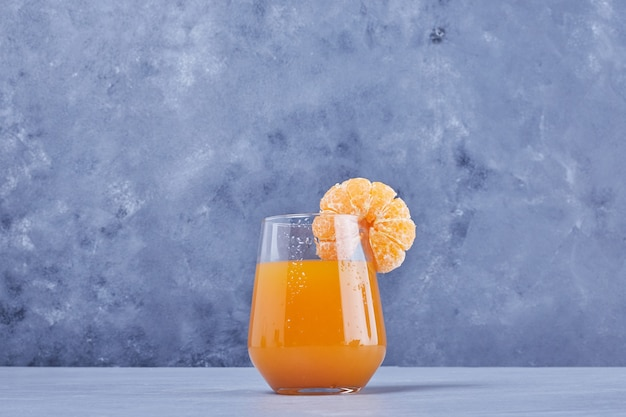 Een glas mandarijnensap met fruit.