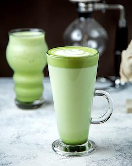 Een glas matcha groene thee met latte kunst erop
