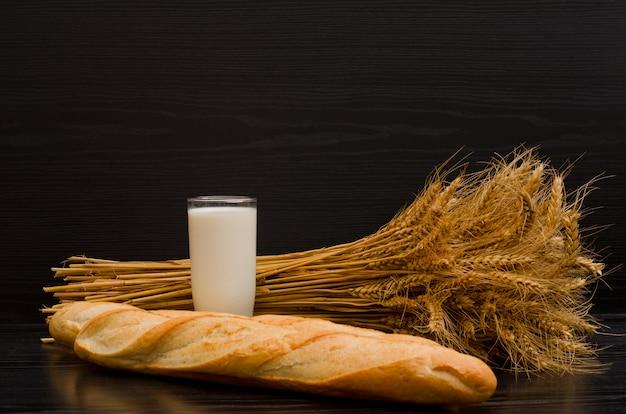 Een glas melk, een brood en een schoof op een zwarte achtergrond, met ruimte voor tekst