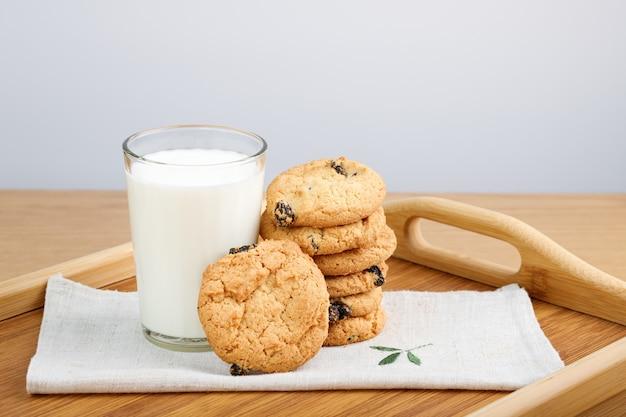 Een glas melk en koekjes met rozijnen op een houten dienblad