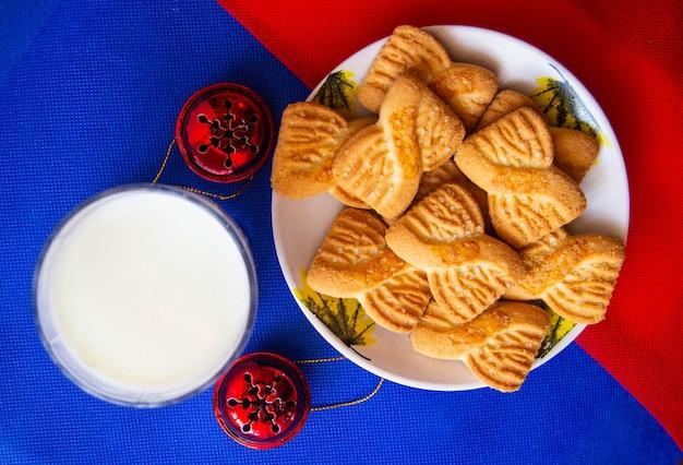 Een glas melk en koekjes of zandkoekjes op het bord met rode belletjes. nationale koekjesdag achtergrond. kerstontbijt voor de kerstman. amerikaans ontbijt
