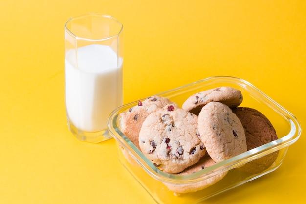 Een glas melk en zelfgemaakte koekjes met stukjes chocolade en rode bosbessen in een glazen voedselcontainer op een geel oppervlak