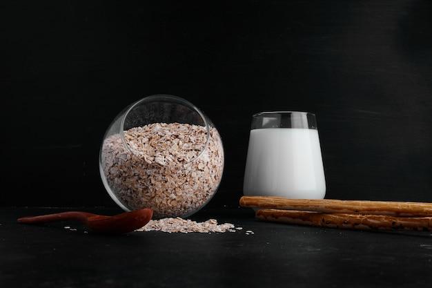 Een glas melk geserveerd met een kopje granen op een zwarte ondergrond.