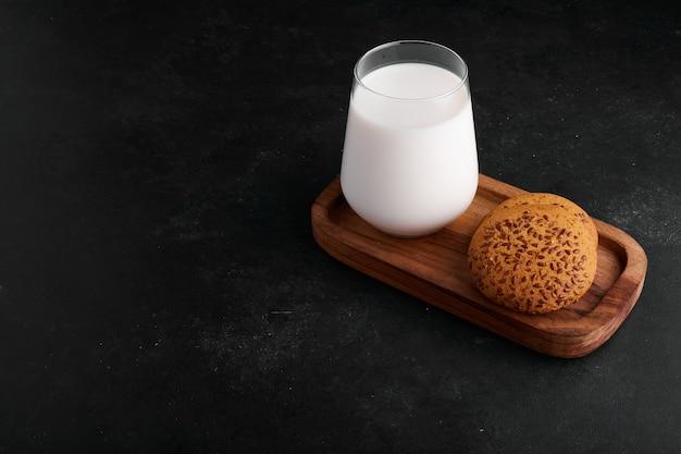 Een glas melk met komijnkoekjes.