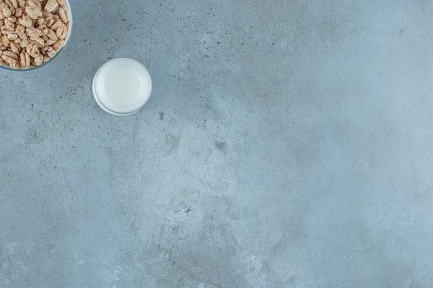 Een glas melk naast cornflakes in een glazen voetstuk, op de marmeren achtergrond.