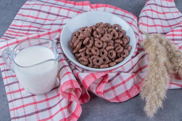 Een glas melk naast maïsringen in een glazen kom naast pampagras op de theedoek, op de marmeren tafel.