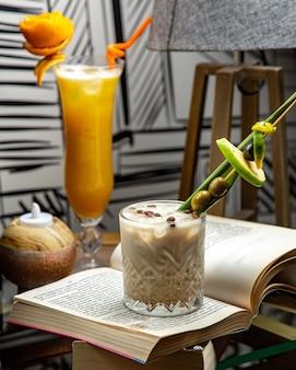 Een glas melkachtige cocktail gegarneerd met olijfappel en koffiebonen