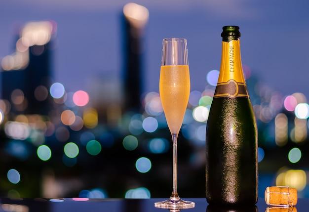 Een glas met damp van koude champagne met fles en kurk op de kleurrijke achtergrond van stadsbokehlichten