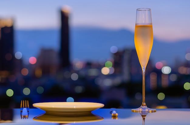 Een glas met damp van koude champagne met schotel om te dineren