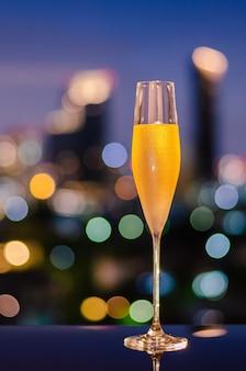 Een glas met damp van koude champagne op tafel met kleurrijke bokeh-verlichting in de stad