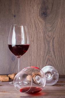 Een glas met de resten rode wijn ligt