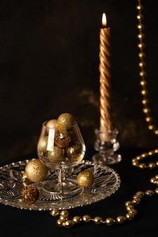 Een glas met gouden nieuwjaarsballen, een kaars en kerstversiering op een donkere achtergrond. hoge kwaliteit foto