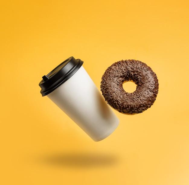 Een glas met koffie en een chocoladedoughnut die tegen een gele achtergrond met een exemplaarruimte zweeft.