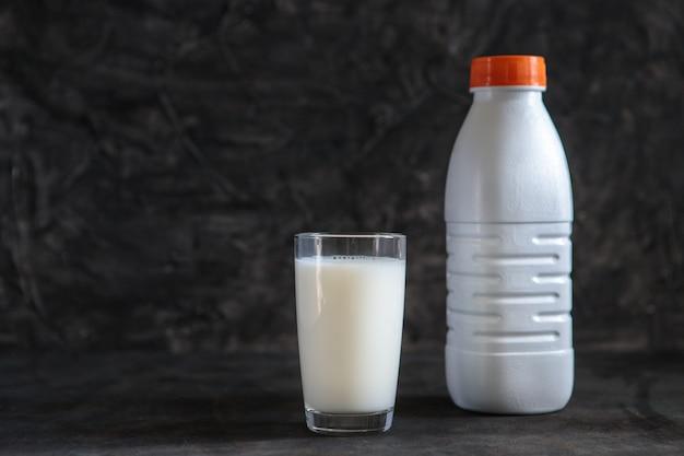 Een glas met melk en een plastic fles witte melk op een zwarte achtergrond. ruimte voor tekst, minimalisme. vloeistof in een plastic container.