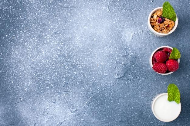 Een glas met yoghurt, muesli en bessen op een grijze achtergrond en een witte plaat