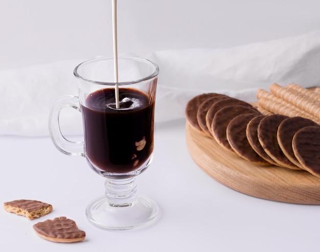 Een glas met zwarte koffie waarin room naast zoete gebakjes op een witte achtergrond wordt gegoten