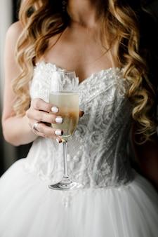 Een glas mousserende wijn in de handen van de bruid
