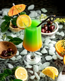 Een glas ombrecocktail met citroenplak