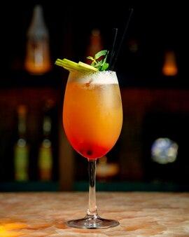 Een glas oranje cocktail gegarneerd met munt en groene appelschijfjes