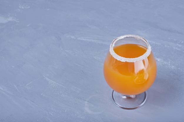 Een glas oranje cocktail.