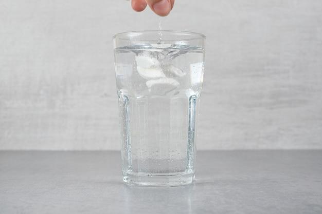 Een glas puur koud water op een grijze ondergrond