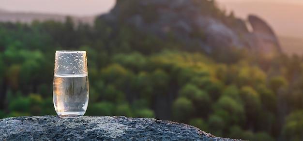 Een glas puur transparant mineraal drinkwater tegen de achtergrond van een zonsondergang in de bergen...