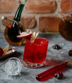 Een glas rode alcoholcocktail met appelplakken en ijsblokjes.
