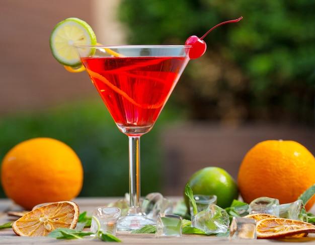 Een glas rode alcoholcocktail met limoenplak en kers